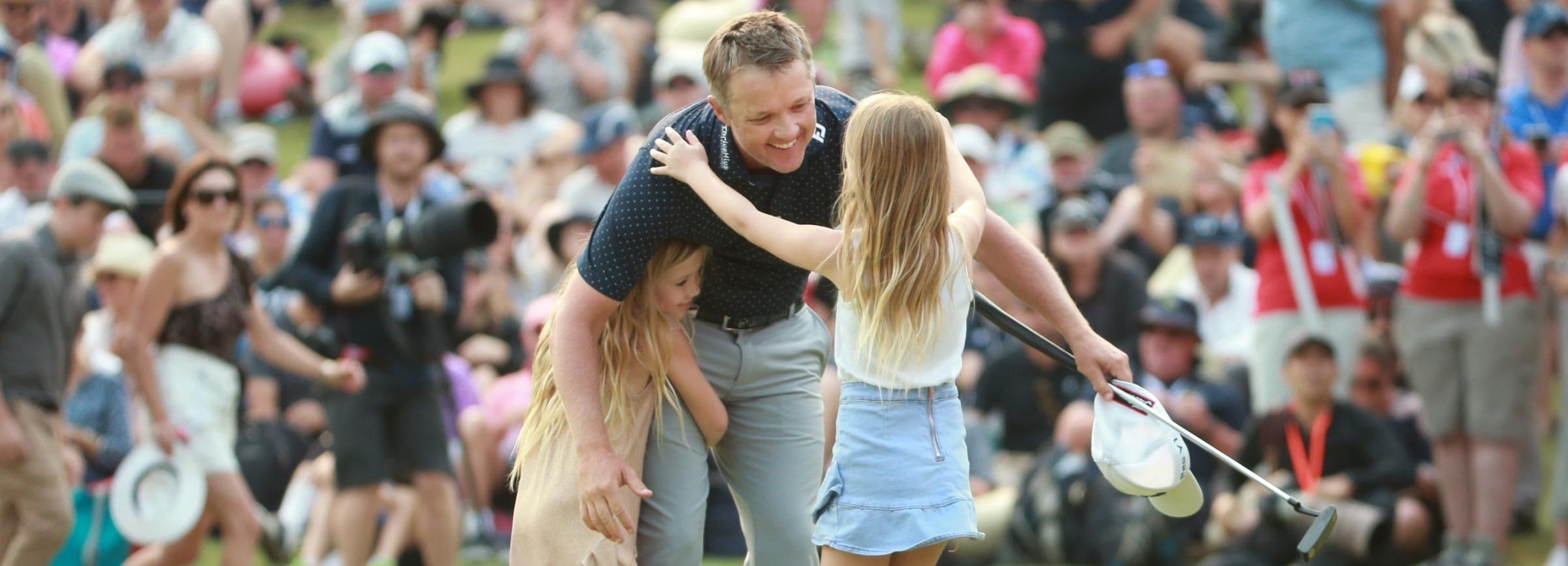 Matt Jones hugs tow of his daughters after sinking the winning putt.