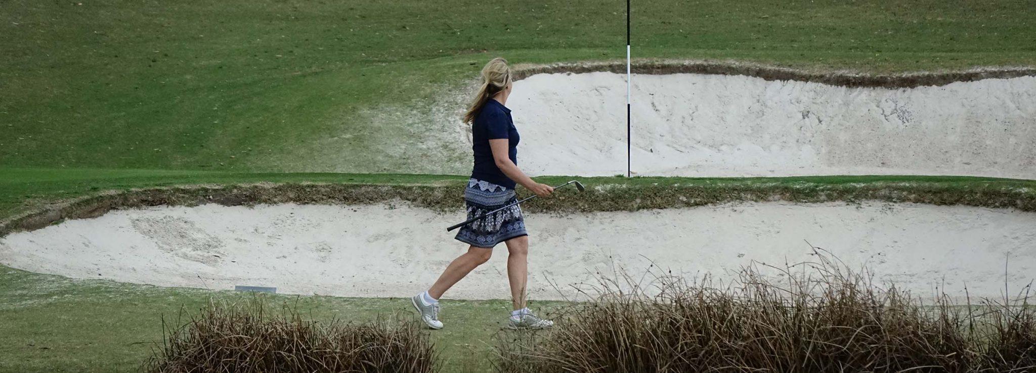 golfer walks past a bunker