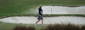 golfer walks past a bunker