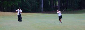 Golfer hitting a shot as caddy looks on