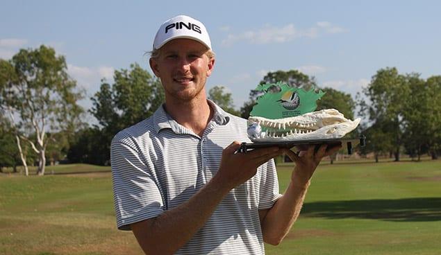 Golfer holding Crocodile skull trophy