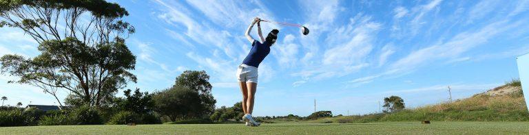 Golfer tees off under a spectacular sky