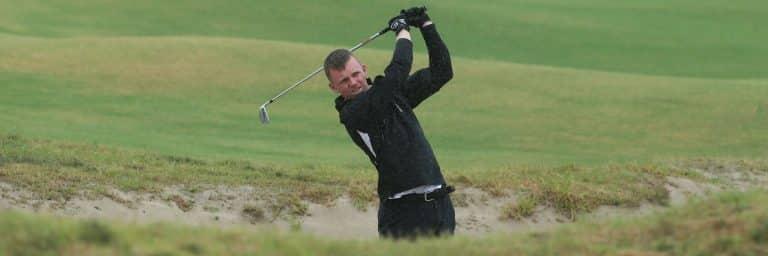 golfer hitting from a bunker